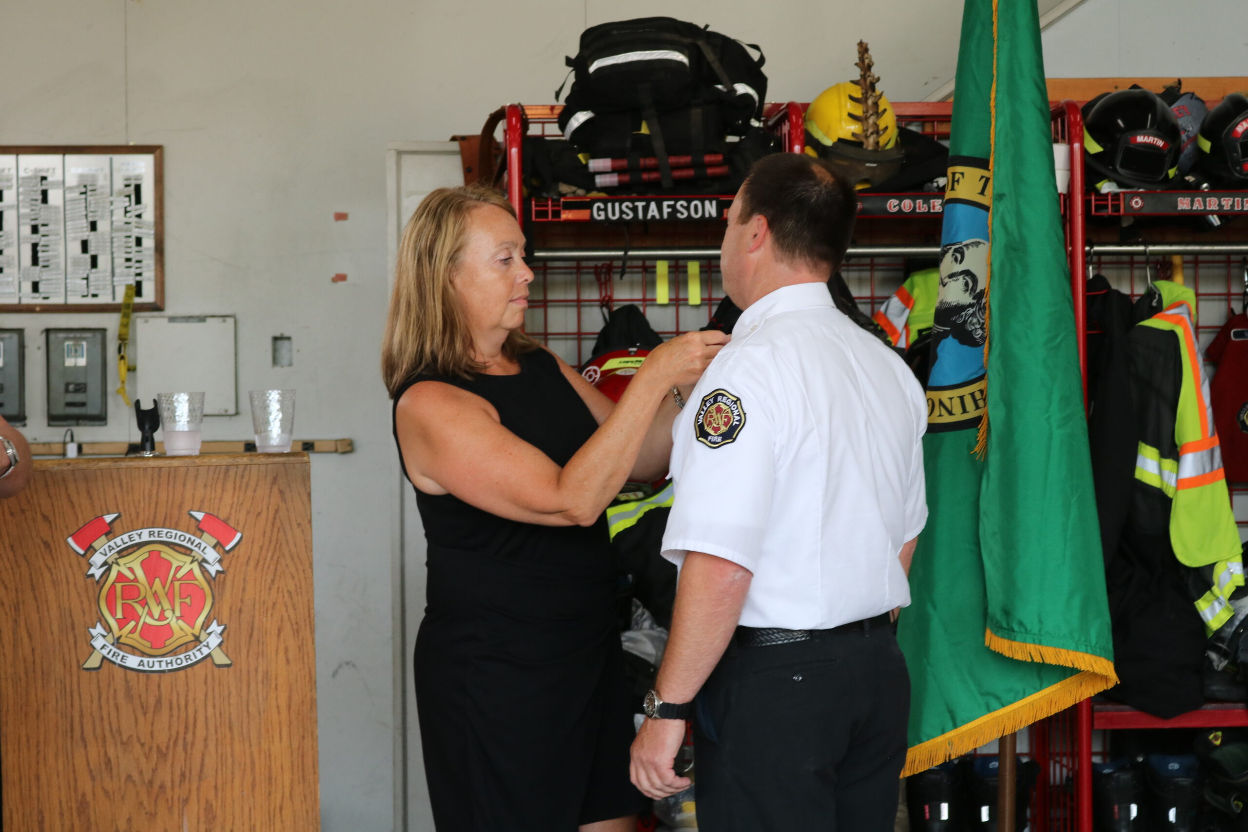 VRFA Chief Brad Thompson receives his Chief's pin, placed on his lapel by his wife.