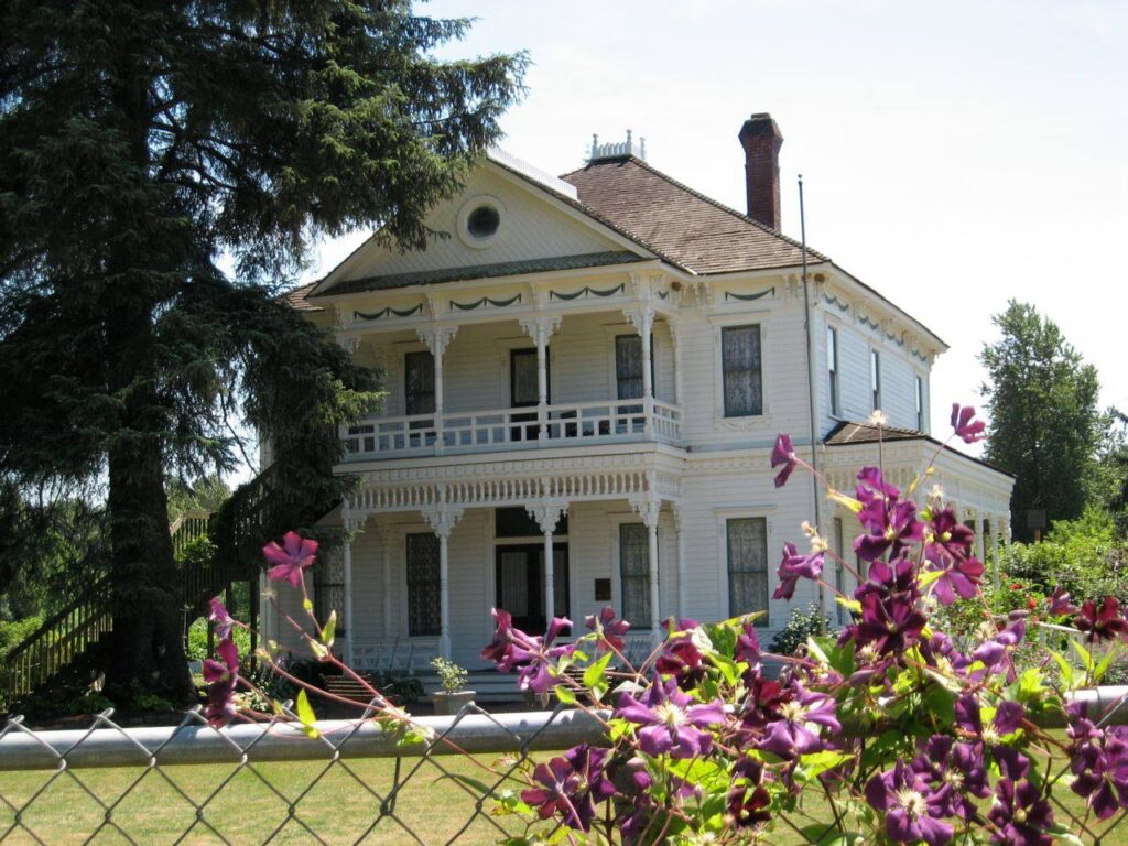 A historic farmhouse, Neely Mansion, with flowers along a chainlink fence in the foreground.