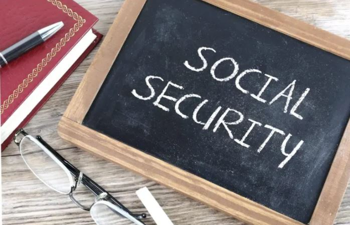 """A handheld chalk board with """"Social Secuirty"""" on it. Next to the chalk board are a pair of glasses and part of a book"""