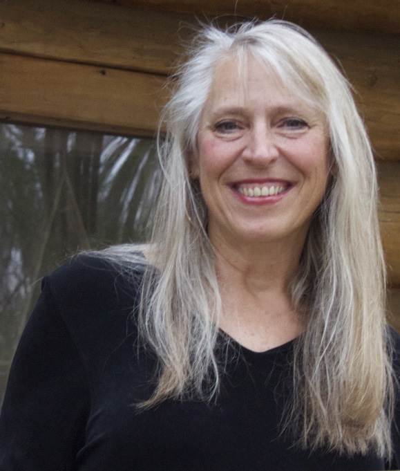 Cindy Ross, a middle-aged white woman with long light blonde hair, smiles widely at the camera white standing in front of a window.