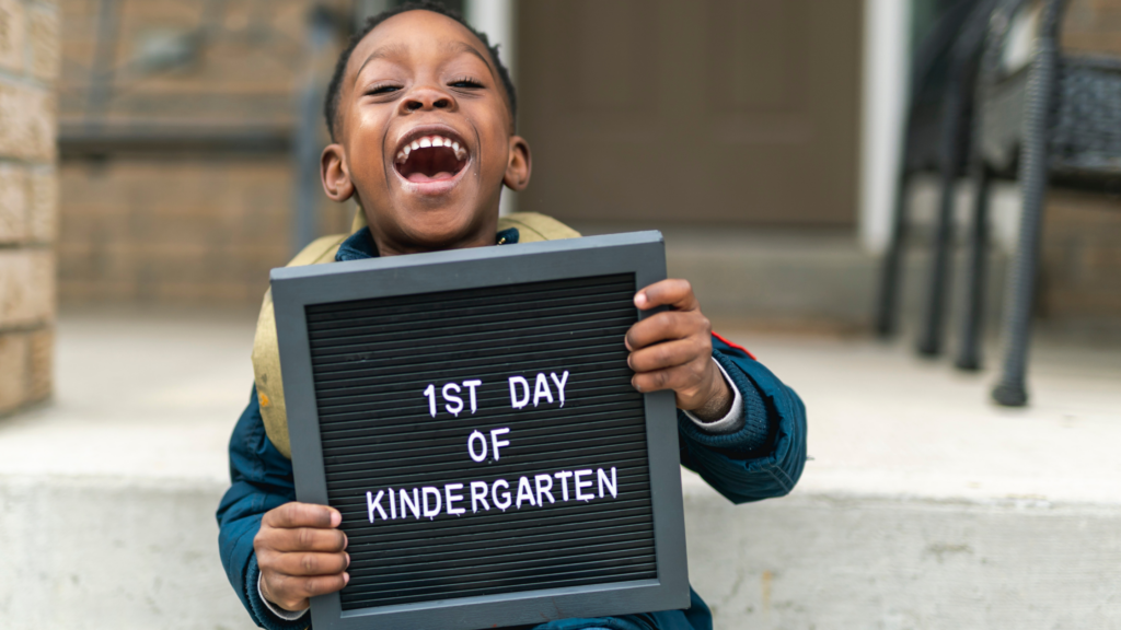 """a laughing child holds a sign that says """"1st day of kindergarten"""""""