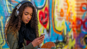 A young female looks at her phone as she listens to music on headphones, she leans against a vibrantly colored mural on a brick wall