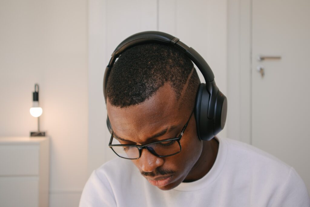 A Black male wearing glasses and a white shirt wearing large headphones looks downward
