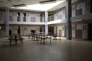 Empty interior of cell block in Correctional Institution, or jail., common room with jail cells.