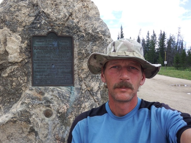Shawn Murphy takes a selfie on a trail next to a marker embedded in a large boulder. He wears a floppy fisherman's bucket hat and a blue t-shirt