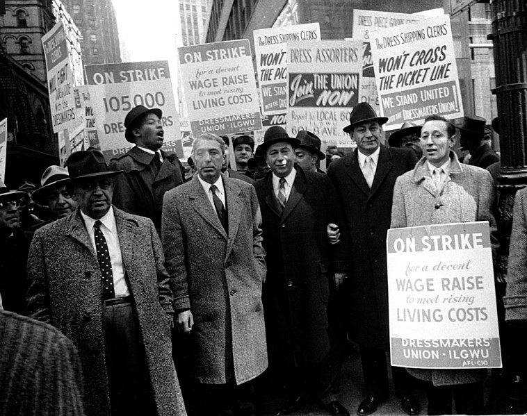 A group of dressmakers on strike hold signs urging unionization and fair labor practices