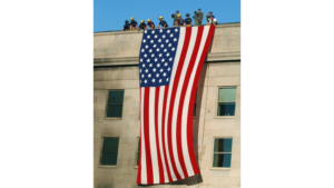 First responders and military personnel drape an american flag over the side of the Pentagon