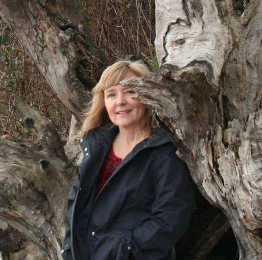 A photo headshot of poet Cindy Hutchings standing by a tree