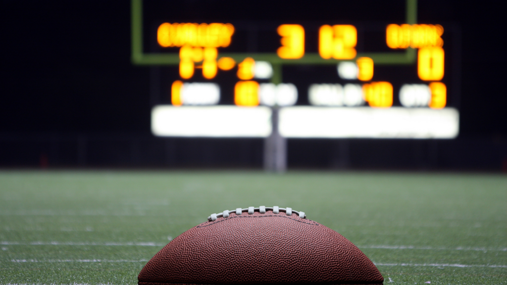 A football in the foreground of a blurred football field and lit up scoreboard
