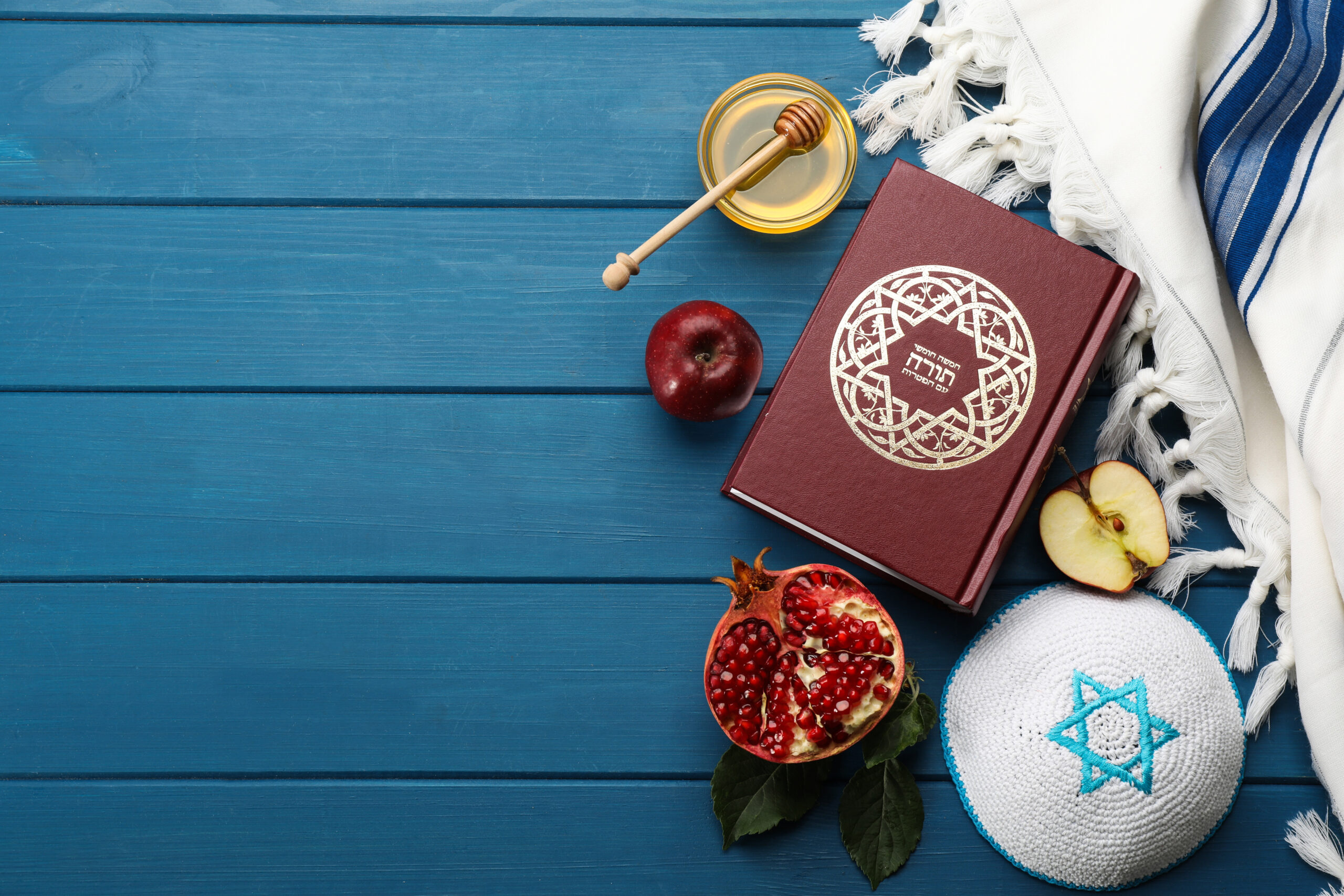 Flat lay composition with Rosh Hashanah holiday attributes on blue wooden table. Torah book with text in hebrew
