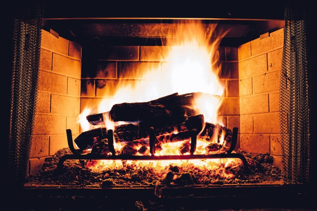 a wood burning fire burns in a fireplace