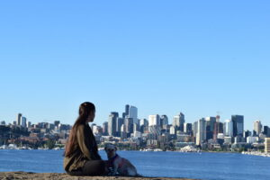 Woman Looking At City Buildings Against Clear Blue Sky