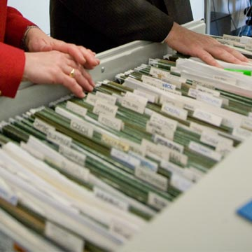 two people look through a large open file drawer
