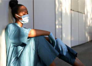 A female medical professional sits on the ground leaning against a wall, visibly tired