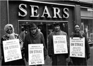 An old photo of a group of male employees in winter coats and striking outside of Sears