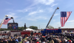 Two large American flags hang from firetruck ladders, a crowd of people listen to names announced from an honor roll of fallen firefighters. Dave Lewis' name and photo are on a jumbo screen at the front of the crowd