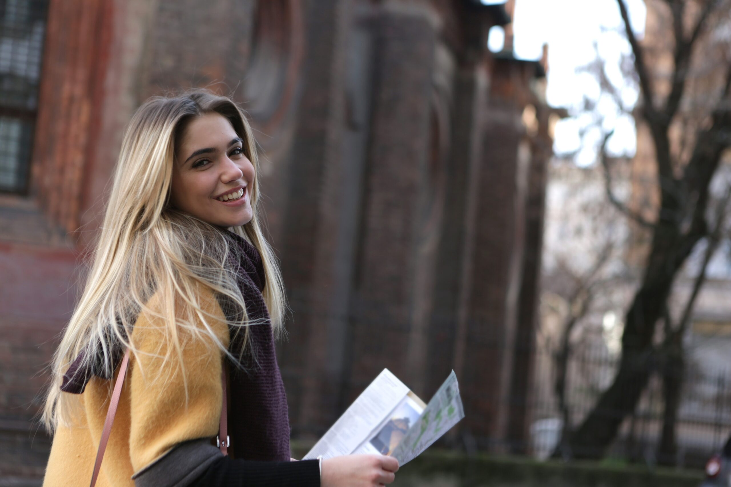 A blonde female holds a map while touring a college campus